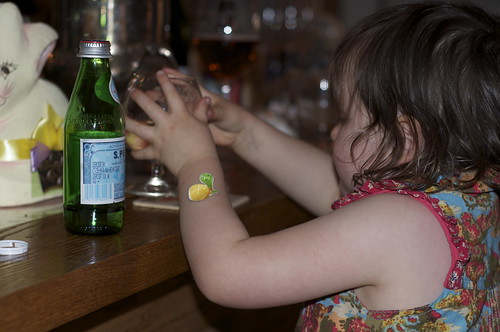 A young child being taught to belly up to the bar. And order a Pellegrino. In a Cognac glass.