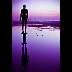 another place (FoxyMcSlick) Tags: sunset shadow sea england sky irish reflection art beach wet public water silhouette liverpool canon eos rebel evening coast interestingness still sand purple pillar kitlens explore anthony windfarm crosby xsi antonygormley formby anotherplace oversharpened explored 450d gormly theperfectphotographer ukstatue foxymcslick