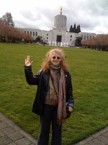 white female with curly hair stands in front of the state capital building in salem oregon