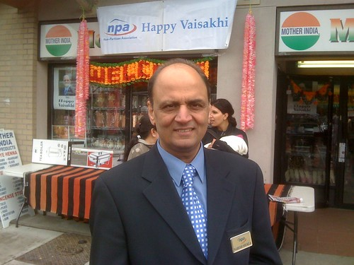 "NPA Director Naresh Shukla standing in front of the NPA's ""booth"" at Vaisahki Day"