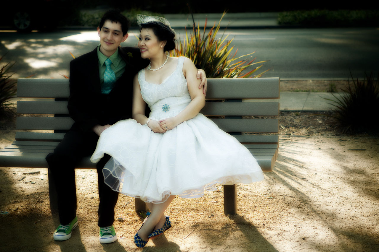 bride and groom on the bench at the park