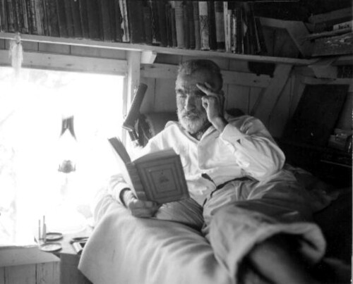 Old hermit Roy Ozmer reading a book at his house: Pelican Key, Florida by State Library and Archives of Florida.