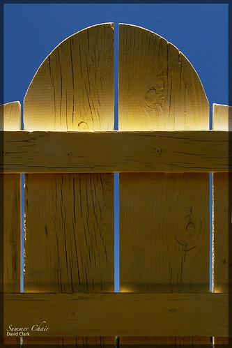 A yellow adirondack chair's back, hilighted by sunlight, against a blue sky.