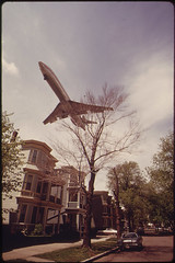 a large airplane flying low over apartments