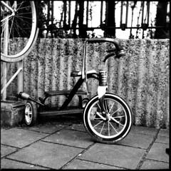 Hotwheels (Arne Kuilman) Tags: bike tricycle vondelpark lock locked amsterdam netherlands nederland blackandwhite zw 6x6 yashica yashica635 mediumformat fiets kinderfiets retroflyer red rood
