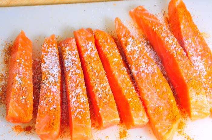 uncooked salmon fish sticks with seasoning