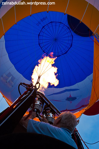 A hot air balloon pilot pumping in the hot air into his balloon envelope