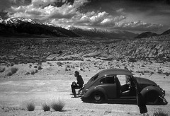 Kevin and the red bug in Monochrome (Bodie Bailey) Tags: california family clouds volkswagen landscape brother roadtrip kodachrome owensvalley 395 highway395 easternsierra alabamahills kevinbailey 64
