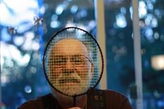 le visage d'un homme à travers une raquette de badminton