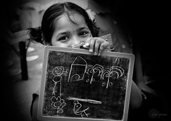 .Education. (.krish.Tipirneni.) Tags: bw india house selfportrait flower cute bird girl smile children blackwhite eyes education nikon pretty child coconut drawings shy looks slate lovely hyderabad andhra educate ngo hpc renuka pradesh educaci 18200vr d80 pilaka kukatpally alambana rtkpeople
