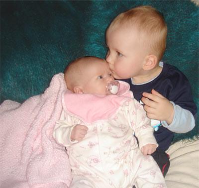 A young boy kisses his new born sister
