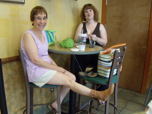 Deb tries on her sock.  Bobbi keeps knitting.