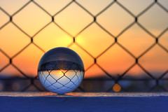 crystal sunset:  131/365 (helen sotiriadis) Tags: blue light sunset orange black canon fence dof bokeh religion science athens depthoffield sphere refraction 365 hdr crystalball canonef50mmf14usm laplace marousi  canoneos40d opticalglass   toomanytribbles  jerrycoyne