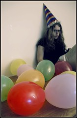 A monochrome unhappy looking woman surrounded by colourful balloons