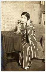 At the Phone in Old Japan (c.1920) (postaletrice) Tags: old woman cute girl beautiful face socks japan lady vintage japanese photo clothing mujer eyes asia call pretty sitting toe chica phone expression antique postcard telephone femme young antigua telfono llamada tabi linda yukata nippon kimono obi oriente asie postal elegant orient delicate armchair calling far japon ropa vtements nihon candlestick postale carte garments ancienne gamine tarjeta tlphone zori telefnica muchacha cpa lejano rppc