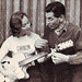 Carolyn Noble as Jim Atkinson tutors her with a guitar