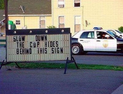 cops hiding behind sign