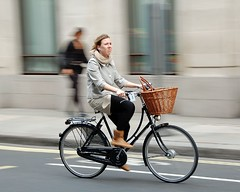 Must be a sad song (jeremyhughes) Tags: city music woman motion blur london bike bicycle scarf movement nikon cyclist ipod basket boots zoom coat explore rack headphones commuter nikkor upright panning vr cityoflondon earbuds mixte sadsong d40 jeremyhughes nikond40 traditionalbicycle