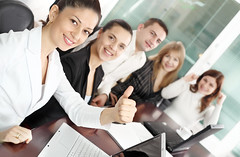 Successful business group. (Heberger Site) Tags: people woman man male girl smile up female work computer happy corporate israel office student team education adult desk contemporary laptop group young plan meeting business suit staff together unite sit workplace thumb conversation explain executive job success colleague partnership partner interaction teamwork caucasian businesspeople occupation associate consultation successful workgroup businessgroup