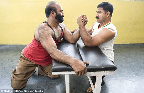 Joby Matthew and an unidentified man arm-wrestle on a weight bench.  The unidentified man, who has a beard and fully developed legs, grips  the far side of the weight bench.  Both men are grimacing and neither  appears to be winning.