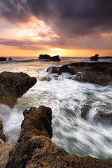 Tanjungan Sunset (tropicaLiving - Jessy Eykendorp) Tags: light sunset sea bali seascape motion west beach nature water clouds canon reflections indonesia landscape eos coast rocks action stones shoreline efs 1022mm tanahlot 50d outdoorphotography canoneos50d tropicaliving hitechfilters rawproccessedwithdigitalphotopro tiffproccessedwithadobephotoshopcs3 tanjungansunset hitechfilterndgrad