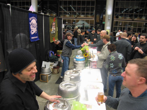 In the foreground, Carter Camp (Port Townsend Brewing) chats with a festivalgoer. In the background, Ed Bennett (Boundary Bay Brewing) hands over the goods to a thirsty fan.