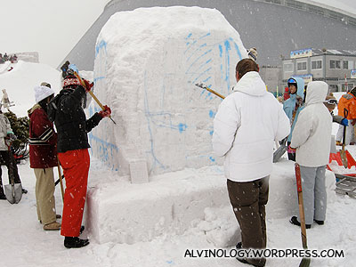 Snow sculpturing contestants slugging it out on their assigned block of snow