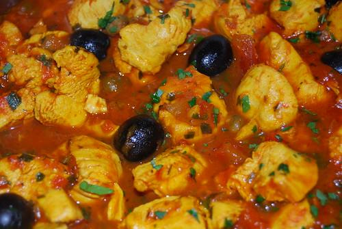 biologische kip met saffraan, tomaat, olijven en kappertjes