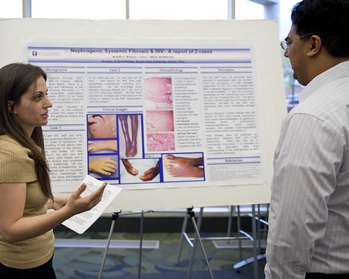 Medical student Melanie Raffoul discusses her poster presentation with Dr. Amol Soin, clinical assistant professor of surgery, at the last year's symposium. [Photo by Will Jones, WSU CTL]]