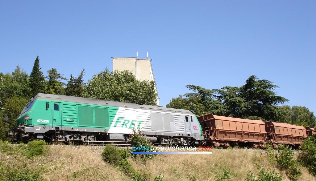 Une locomotive Diesel-électrique BB 475000 en tête d'un convoi de wagons minéraliers de bauxite
