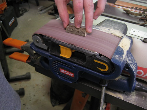sanding down a short piece along its split face on my belt sander