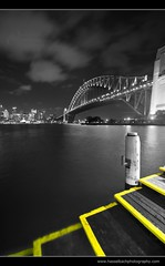 Australia - Sydney Harbour Bridge (Hasselbach Photography) Tags: city travel bridge blue sea vacation sky urban bw colour reflection history tourism water yellow horizontal skyline architecture night effects lights evening cityscape arch place symbol harbour steel south famous sydney australian arc australia landmark icon tourist structure quay illuminated land destination sydneyharbourbridge placeofinterest colourpopping flickrexportdemo ryanhasselbach hasselbachphotography