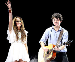 Nick Jonas and Miley Cyrus Singing Their New Duet Before the Storm at the Jonas Brothers Concert in Texas (i <3 nick jonas!!!) Tags: storm lights concert dress singing guitar stage nick before microphone cyrus jonas curlyhair miley whitedress stage