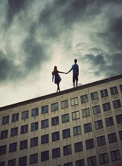 Together we stand, alone we fall (miriness) Tags: sky fall clouds photoshop dark jump couple dramatic surreal strength holdinghands dreamscape lean boyandgirl emontional madewithstockimages standingontopofabuilding