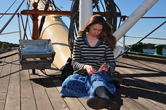 Steph sitting on the Pommern deck putting together the Yoda figure