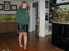 Weird, Sarah is actually smiling by looking at the fish tank.... that does NOT happen much these days. My only explanation is that she must have just reached in her pocket and discovered an uneaten piece of Alphabits. (colorblindPICASO) Tags: smiling sarah walking longhair hallway fishtank barefoot barefeet inuyasha greenhoodie blondhair handsinpockets hairdown lookingover blackshorts feetcrossed