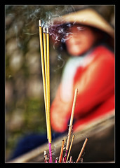 with a prayer in her heart.. (PNike (Prashanth Naik..back after ages)) Tags: blue red woman hat lady temple pagoda nikon vietnamese bokeh prayer vietnam lá hue incense incensesticks nón d3000 pnike