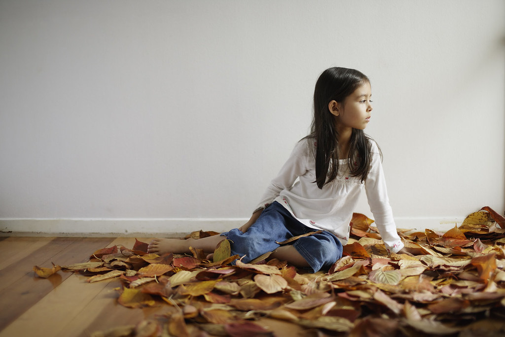 Five year old girl sitting in hall with autumn leaves. Childhood, contemplation, innocence.