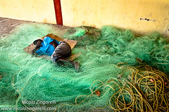 Port Blair, Andaman Islands. India. Man sleeping over the fishing nets (Nicola Zingarelli) Tags: sleeping india man net abandoned port fishing fisherman harbour sleep indian homeless poor indianocean dreaming tired ropes nets andaman fishingnets sleeeping andamans andamanislands portblair chathambay gillnets andamanisland gulfofbengala