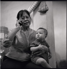 Yao Bang + Granny (who is busy talking over the phone) (S.H.CHOW) Tags: 6x6 rolleiflex mediumformat blackwhite fuji kodak hc110 neopan pushed neopan400 ilford f28 iso1600 schneider 80mm fujineopan400 selfdeveloped xenotar 28e 13mins dilutionh rolleiflex28e 2stops autaut bathroomdevelopment kodakhc110163 295c agitatefirstminute