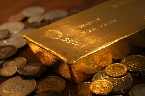 Shiny gold bar reflecting coins