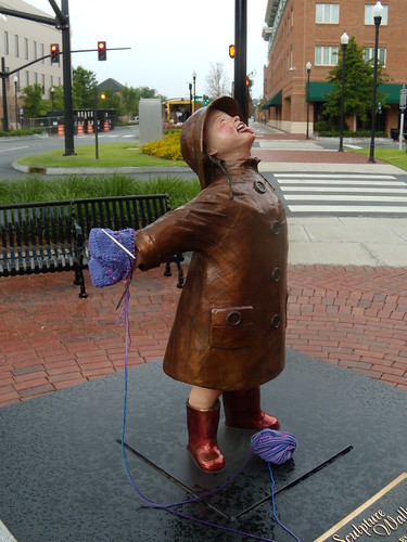 Girl in the rain statue with yarn