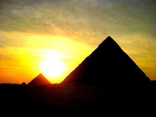 the sun sets behind the great pyramids