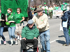 Wheelchair parader during the St. Patrick's Day parade. (kennethkonica) Tags: old irish usa men green america women midwest sitting sweaters indianapolis seat wheelchair hats parades indiana jeans elderly sit seated jackets hoosiers seniorcitizens stpatrickday