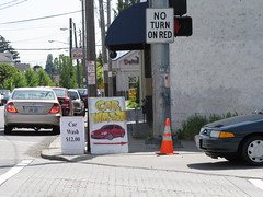 Two sidewalk signs in the right-of-way at 15th and Beacon. The car on the right is about to enter the intersection (and crosswalk) and make an illegal right turn onto 15th (the light was red by the time they made the turn, and the intersection is No Right on Red.) Photo by Wendi.