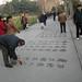 085cgold man writing calligraphy on sidewalk