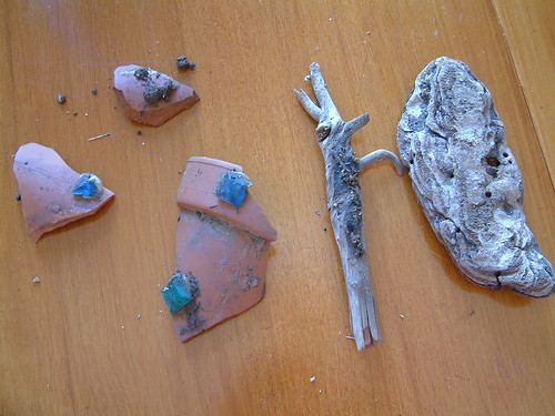 Broken pottery, stick and piece of bark