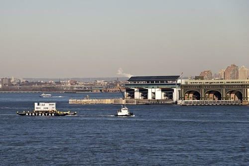 The house was pulled by a tug past the Battery, with the Staten Island Ferry and Battery Maritime buildings visible in the background.
