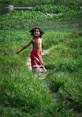 Bangladesh! (AvikBangalee) Tags: poverty playing nature girl smile grass river hair kid nikon child natural happiness dhaka tamron 18200 bangladesh redskirt lightroom redandgreen nationalflag d90 explored f3563 keraniganj poorestnation