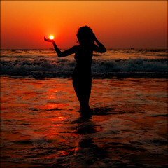 A Mermaid and the Sun (JannaPham) Tags: ocean sunset sea vacation sun india holiday beach girl silhouette sunrise canon eos evening hand goa mermaid majorda 40d jannapham